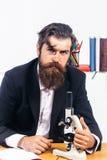Серьезный человек работает с микроскопом Стоковые Изображения RF