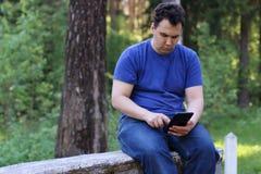 Серьезный человек сидит на каменной стене и работает с ПК таблетки Стоковая Фотография