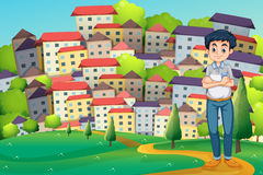 Серьезный человек стоя на вершине холма через деревню Стоковое Фото