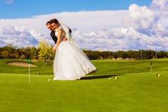 Серьезный groom и невеста играя гольф стоковое изображение rf