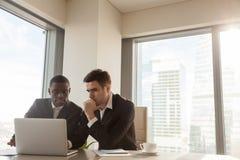 2 серьезных бизнесмена обсуждая проект в офисе, используя lapt Стоковое фото RF
