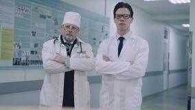 2 серьезных доктора смотря камеру в медицинском офисе 4K сток-видео