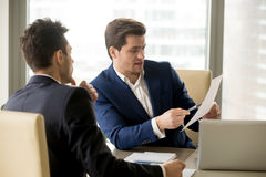 2 серьезных делового партнера обсуждая документ, бизнесменов n Стоковые Изображения RF