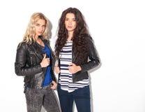 2 серьезных молодой женщины в кожаных куртках держа их воротники Стоковые Фото