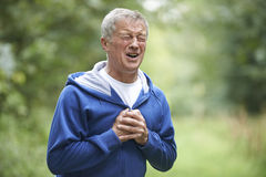 Сердечный приступ старшего человека страдая пока Jogging стоковое изображение
