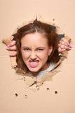 Сердитая девушка смотря прищурясь через отверстие в бумаге Стоковые Изображения RF