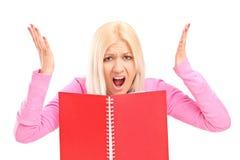 Сердитая девушка читая книгу Стоковые Изображения