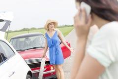 Сердитая женщина готовя поврежденные автомобили при женщина используя сотовый телефон в переднем плане Стоковые Фотографии RF