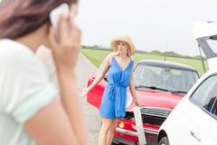 Сердитая женщина готовя поврежденные автомобили при женщина используя сотовый телефон в переднем плане Стоковая Фотография