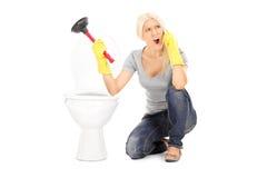Сердитая женщина держа плунжер и говоря на телефоне Стоковые Фотографии RF