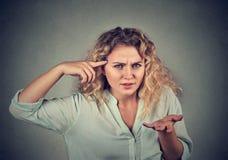 Сердитая женщина показывать против виска вы шальные? стоковое фото