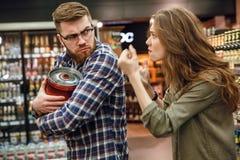 Сердитая женщина пробуя принять далеко от пива бочонка человека Стоковое Изображение RF