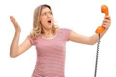 Сердитая женщина проводя диктора телефона стоковые изображения rf
