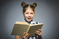 Сердитая или усиленная девушка с книгой ребенок на серой предпосылке концепция исследований стоковые изображения