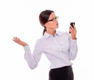 Сердитая коммерсантка брюнет с сотовым телефоном Стоковые Фотографии RF