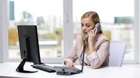 Сердитая коммерсантка с компьютером вызывая на телефоне видеоматериал