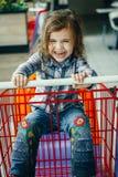 Сердитая маленькая девочка сидя в магазинной тележкае стоковое фото rf