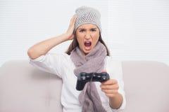 Сердитое брюнет с шляпой зимы на играть видеоигры Стоковые Изображения