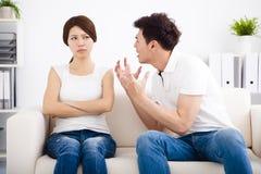 Сердитые молодые пары сидя на софе стоковая фотография
