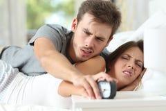Сердитые пары поворачивая будильник стоковые изображения