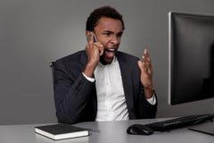Сердитый африканский человек на его телефоне стоковое изображение