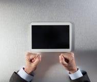 Сердитый бизнесмен вручает выражать нетерпение, фрустрацию или стресс смотря на таблетку стоковое фото