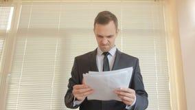 Сердитый бизнесмен в офисе, складывает вверх документы штабелирует вверх видеоматериал