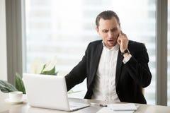 Сердитый бизнесмен говоря на мобильном телефоне Стоковые Фотографии RF