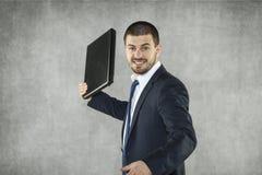 Сердитый бизнесмен готовый для того чтобы разрушить компьтер-книжку стоковые фотографии rf