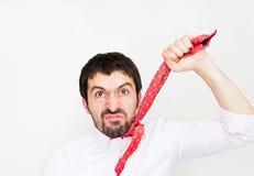 Сердитый бизнесмен держа его связывает вверх стоковое фото rf