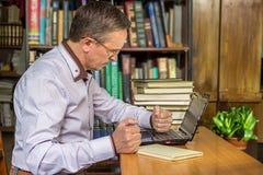 Сердитый бизнесмен пробивает его компьютер после получать расстроен Стоковое фото RF