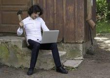 Сердитый бизнесмен работая на компьютере пока сидящ на ste Стоковые Изображения