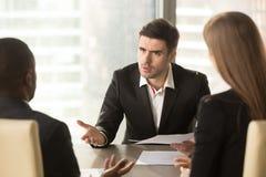 Сердитый босс неудовлетворенный с плохим результатом, партнеры споря около Стоковое Изображение