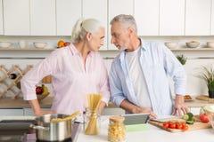 Сердитый зрелый человек стоя около зрелой серьезной женщины на кухне Стоковая Фотография