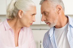 Сердитый зрелый человек стоя около зрелой серьезной женщины Стоковое Изображение
