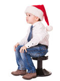 Сердитый малыш в шлеме santa на стуле Стоковые Изображения