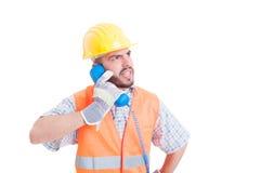 Сердитый построитель имея переговор на телефоне стоковые изображения rf