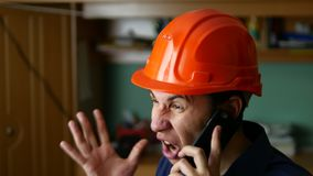 Сердитый рабочий-строитель человека в защитном шлеме крича, говоря на smartphone телефона стоковое фото rf