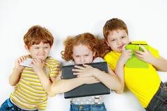 Сердитый друг детей твердо держит его smartphone, тетради Стоковые Фотографии RF