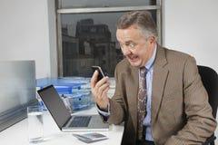 Сердитый средн-постаретый бизнесмен смотря сотовый телефон в офисе Стоковое Изображение RF