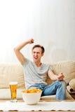 Сердитый человек кричащий пока смотреть резвится на ТВ Стоковые Фото