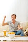 Сердитый человек кричащий пока смотреть резвится на ТВ Стоковое Фото