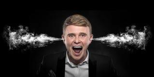 Сердитый человек при дым приходя вне от его ушей стоковая фотография