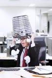 Сердитый ящик хлама владением бизнесмена на его голове на офисе Стоковые Фотографии RF