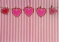Сердца валентинки вися от шпагата на красной Striped предпосылке Стоковые Изображения RF