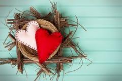 2 сердца войлока в деревенском деревянном гнезде Стоковые Изображения