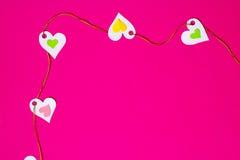 Сердца в ряд, верхний левый угол, на розовой предпосылке Стоковые Изображения