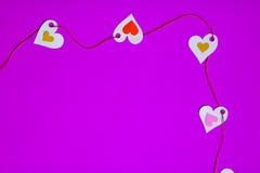 Сердца в ряд, верхний левый угол, на фиолетовой предпосылке Стоковые Изображения