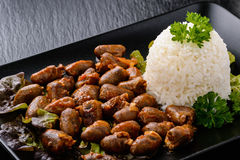 Сердца жареной курицы с рисом на черной плите стоковые фото