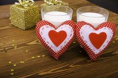 2 сердца и 2 золотых подарка и 2 стекла молока Стоковая Фотография